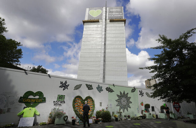 A man looks at tributes placed near Grenfell Tower in London, Sunday, June 14, 2020. Britain is marking the third anniversary of the Grenfell Tower fire with a virtual church service to remember the 72 people who died in the blaze. Sunday marks three years since a small kitchen fire in the west London public-housing block turned into the worst domestic blaze in the country since World War II. (AP Photo/Kirsty Wigglesworth)