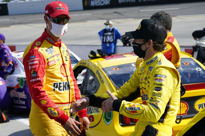 Joey Logano, left, and Ryan Blaney, right talk on pit row prior to the start of the NASCAR Cup Series auto race at Martinsville Speedway in Martinsville, Va., Sunday, April 11, 2021. (AP Photo/Steve Helber)