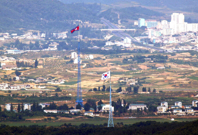Flags of North Korea, rear, and South Korea, front, flutter in the wind in this photo taken from Paju, South Korea, Friday, June 19, 2020. The North in recent months has virtually cut off all cooperation with the South while expressing frustration over Seoul's unwillingness to break away from ally Washington and restart inter-Korean economic projects held back by U.S.-led sanctions over its nuclear weapons program. (Seoul Myung-gon/Yonhap via AP)