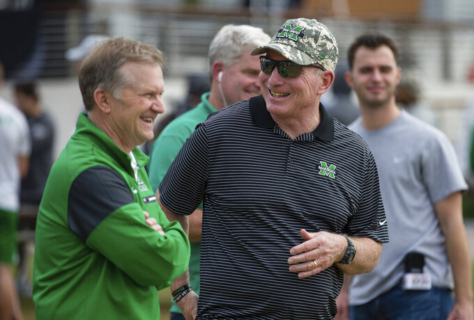 Marshall head coach Doc Holliday, right, laughs with associate athletics director David Steele as players participate in the OnBikes Player Build as part of a Gasparilla Bowl NCAA college football event Friday, Dec. 20, 2019, at Curtis Hixon Park in Tampa, Fla. (Sholten Singer/The Herald-Dispatch via AP)