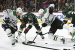 Dallas Stars' Corey Perry (10) falls to the ice while going after the puck against Minnesota Wild's Eric Staal (12) and Mats Zuccarello (36) in the second period of an NHL hockey game Saturday, Jan. 18, 2020, in St. Paul, Minn. (AP Photo/Stacy Bengs)
