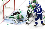 Dallas Stars goaltender Anton Khudobin (35) makes a save against the Tampa Bay Lightning as players scramble in front during third-period NHL Stanley Cup finals hockey action in Edmonton, Alberta, Saturday, Sept. 19, 2020. (Jason Franson/The Canadian Press via AP)