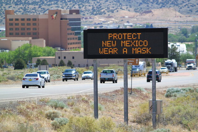 In this May 7, 2020, photo, an electronic highway message board in Rio Rancho, New Mexico, encourages people to wear masks during the coronavirus public health emergency. (AP Photo/Susan Montoya Bryan)