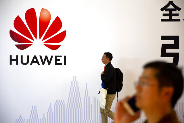 In this Oct. 31, 2019 photo, man uses his smartphone as he stands near a billboard for Chinese technology firm Huawei at the PT Expo in Beijing. Chinese tech giant Huawei kept its global business growing for almost a decade while Washington piled sanctions on the company and lobbied its allies to keep the company out of telecom networks. Now, Huawei is starting to suffer in earnest as the Trump administration steps up efforts to slam the door on access to Western components and markets in a widening feud with Beijing over technology and security. (AP Photo/Mark Schiefelbein)