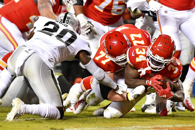 Kansas City Chiefs running back Darwin Thompson (34) scores a touchdown in front of offensive guard Andrew Wylie (77) and Oakland Raiders cornerback Daryl Worley (20) during the second half of an NFL football game in Kansas City, Mo., Sunday, Dec. 1, 2019. (AP Photo/Ed Zurga)