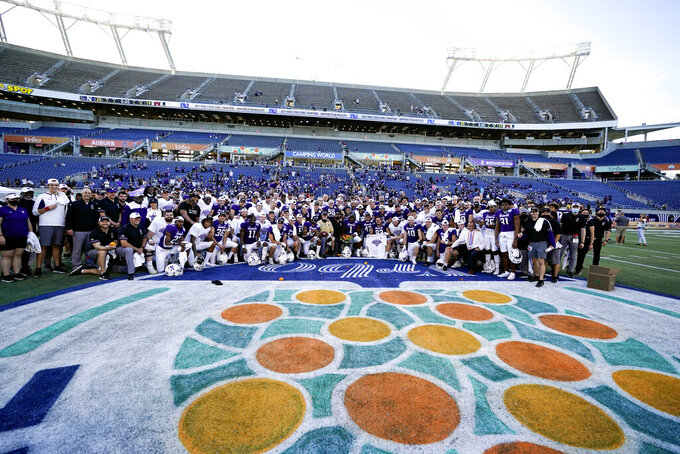 Northwestern coaches, players and personnel gather for a photo after winning the Citrus Bowl NCAA college football game against Auburn, Friday, Jan. 1, 2021, in Orlando, Fla. Northwestern beat Auburn 35-19. (AP Photo/John Raoux)