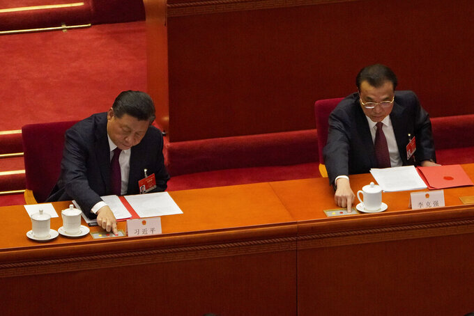 Chinese President Xi Jinping, left, and his Premier Li Keqiang cast their vote during the closing session of the National People's Congress (NPC) at the Great Hall of the People in Beijing, Thursday, March 11, 2021. China's ceremonial legislature on Thursday endorsed the ruling Communist Party's latest move to tighten control over Hong Kong by reducing the role of its public in picking the territory's leaders. (AP Photo/Sam McNeil)