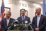 Oklahoma Attorney General Mike Hunter, center, smiles as he answers a question during a news conference following the announcement of the Opioid Lawsuit decision in Norman, Okla., Monday, Aug. 26, 2019. With him are state's attorneys Michael Burrage, left, and Brad Beckworth, right. (AP Photo/Sue Ogrocki)