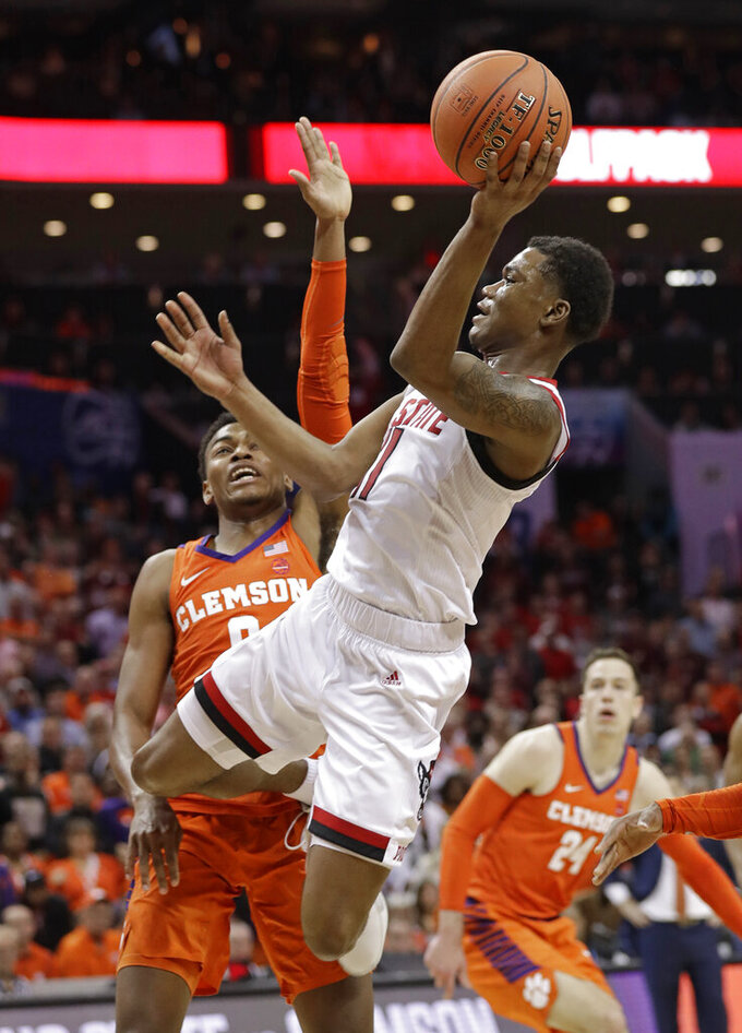 North Carolina State's Markell Johnson, right, shoots over Clemson's Clyde Trapp, left, in the final seconds of the second half of an NCAA college basketball game in the Atlantic Coast Conference tournament in Charlotte, N.C., Wednesday, March 13, 2019. Trapp was called for a foul on the play. (AP Photo/Chuck Burton)