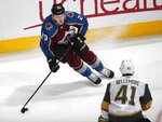 Colorado Avalanche center Nathan MacKinnon, top, looks to pass the puck as Vegas Golden Knights center Pierre-Edouard Bellemare defends during the first period of an NHL hockey game Wednesday, March 27, 2019, in Denver. (AP Photo/David Zalubowski)