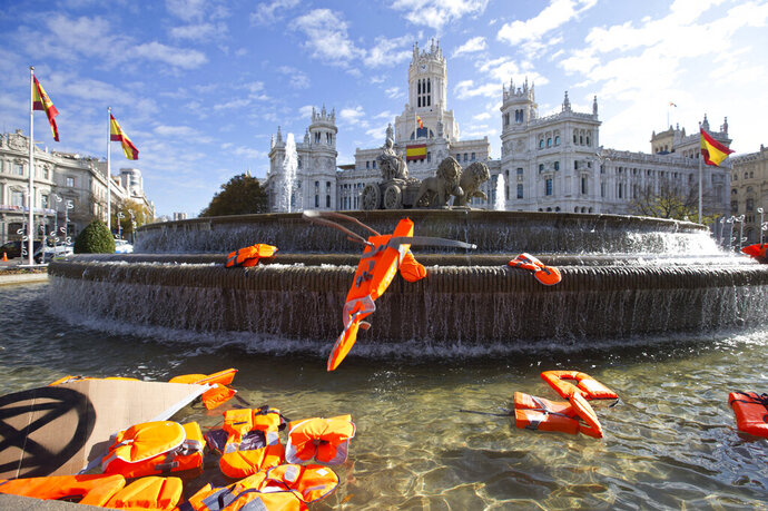 Lifejackets are thrown into the Cibeles fountain during a protest performance in Madrid, Spain, Tuesday, Dec. 3, 2019. Some 20 activists from the international group called Extinction Rebellion cut off traffic in central Madrid and staged a brief theatrical performance to protest the climate crisis. The activists held up a banner in Russian that read