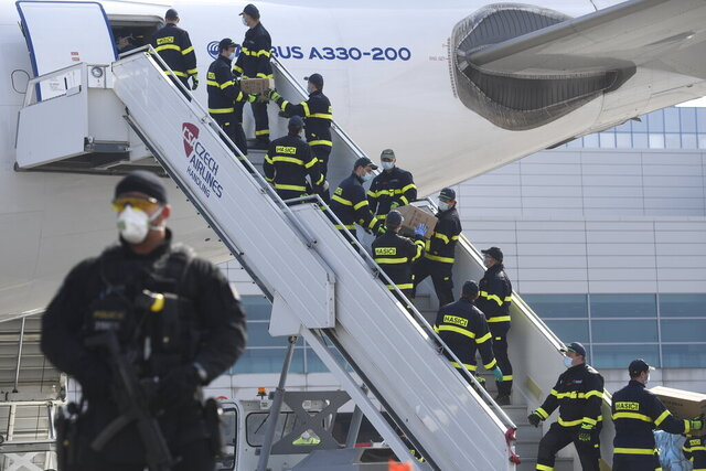 A police officer holds a gun as firefighters unload an airplane after its arrival at the Vaclav Havel Airport in Prague, Friday, March 20, 2020. The airplane brought medical aid and protective materials against coronavirus from China. (Michal Kamaryt/CTK via AP)