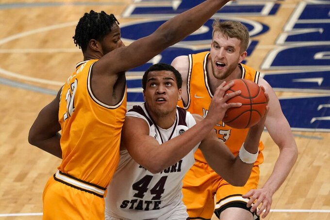 Missouri State's Gaige Prim (44) looks to the basket as Valparaiso's Mileek McMillan, left, and Ben Krikke defend during the first half of an NCAA college basketball game in the quarterfinal round of the Missouri Valley Conference men's tournament Friday, March 5, 2021, in St. Louis. (AP Photo/Jeff Roberson)