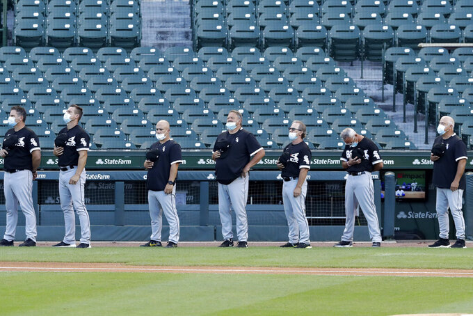 Chicago White Sox manager Rick Renteria, right, and his coaching staff stand for the national anthem before an exhibition baseball game against the Chicago Cubs at Wrigley Field in Chicago, Sunday, July 19, 2020. (AP Photo/Nam Y. Huh)