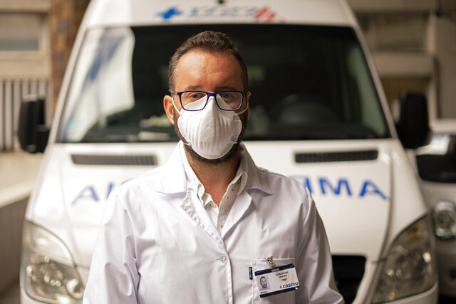 Doctor Sebastian Yancev, who participated in the operation to diagnose and treat passengers on the Australian Greg Mortimer cruise ship for the new coronavirus, poses for a photo in front of the ambulance that was used to move the patients to local hospitals in Montevideo, Uruguay, Tuesday, April 7, 2020. (AP Photo/Matilde Campodonico)