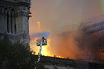 A firefighter uses a hose as Notre Dame cathedral burns in Paris, Monday, April 15, 2019. A catastrophic fire engulfed the upper reaches of Paris' soaring Notre Dame Cathedral as it was undergoing renovations Monday, threatening one of the greatest architectural treasures of the Western world as tourists and Parisians looked on aghast from the streets below. (AP Photo/Francois Mori)
