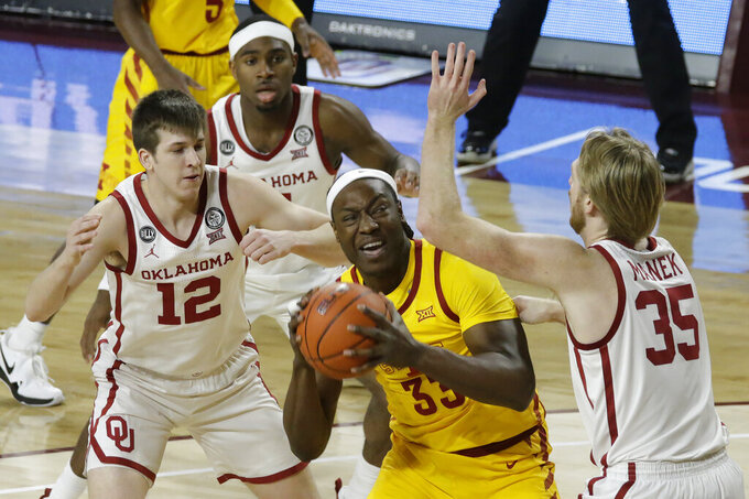 Iowa State's Solomon Young (33) goes against Oklahoma's Brady Manek (35), Austin Reaves (12), and De'Vion Harmon (11) during the first half of an NCAA college basketball game in Norman, Okla., Saturday, Feb. 6, 2021. (AP Photo/Garett Fisbeck)