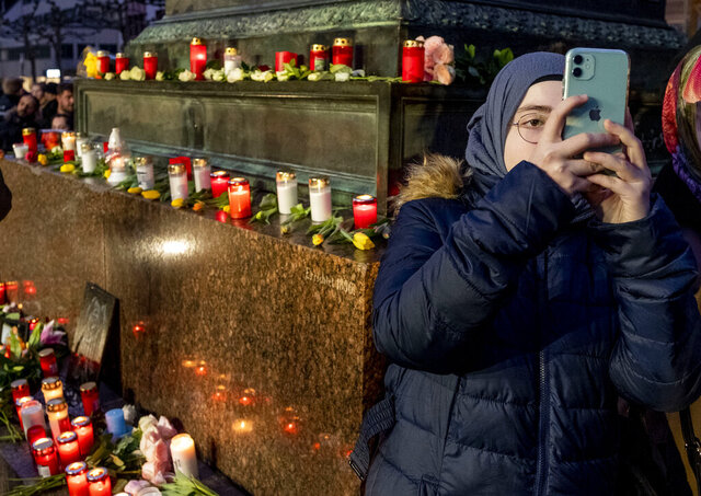 A girl takes a picture near candles as she takes part in a vigil for the victims of a shooting in Hanau, Germany Thursday, Feb. 20, 2020. A 43-year-old German man shot and killed nine people at several locations in a Frankfurt suburb overnight in attacks that appear to have been motivated by far-right beliefs, officials said Thursday.  (AP Photo/Michael Probst)