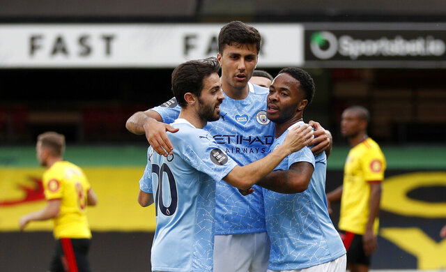 Manchester City's Raheem Sterling, right, celebrates with teammates after scoring his side's opening goal during the English Premier League soccer match between Watford and Manchester City at the Vicarage Road Stadium in Watford, England, Tuesday, July 21, 2020. (Adrian Dennis/Pool via AP)