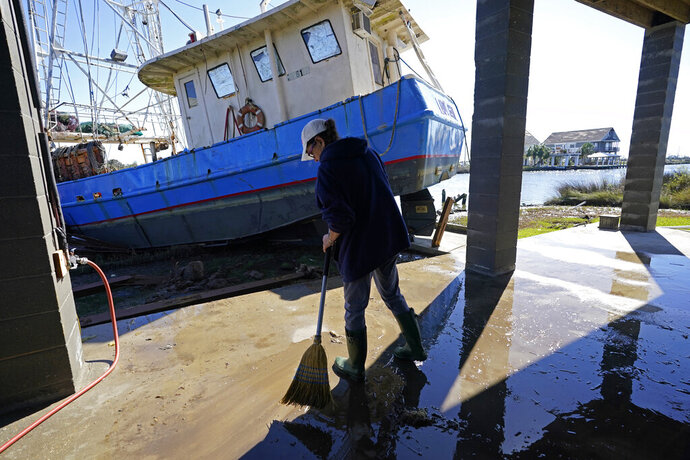 Ray Garcia sweeps water from her home after a boat washed up against it, in Lakeshore, Miss., Thursday, Oct. 29, 2020. Hurricane Zeta passed through Wednesday with a tidal surge that caused the boat to become unmoored. (AP Photo/Gerald Herbert)