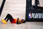 Utah Jazz's Donovan Mitchell lies on the court after being fouled during the second half of an NBA basketball first round playoff game against the Denver Nuggets Sunday, Aug. 23, 2020, in Lake Buena Vista, Fla. (AP Photo/Ashley Landis, Pool)