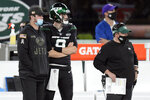 FILE - In this Monday, Nov. 9, 2020, file photo, New York Jets quarterback Sam Darnold, left, looks on from the sidelines during the first half of an NFL football game against the New England Patriots in East Rutherford, N.J. Darnold could be getting closer to returning to the huddle. The Jets quarterback was expected to be limited in practice Wednesday, but there's optimism Darnold's injured right shoulder might be healed in time to play against the Miami Dolphins on Sunday at home. (AP Photo/Bill Kostroun, File)