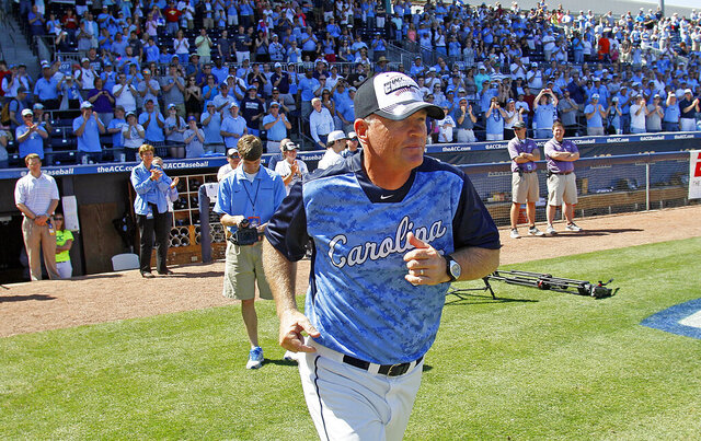 FILE - In this May 26, 2013, file photo, North Carolina head coach Mike Fox takes the field to accept the championship trophy following UNC's 4-1 win over Virginia Tech in an Atlantic Coast Conference NCAA college baseball game in Durham, N.C. UNC announced Friday, Aug. 7 2020, that Fox would retire after 22 seasons at his alma mater that included seven trips to the College World Series. Longtime assistant Scott Forbes is taking over the program. (AP Photo/Karl B DeBlaker, File)