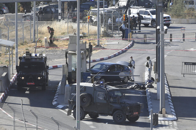 Israeli policemen stand around the body of a Palestinian at a checkpoint near Jerusalem, Tuesday, June 23, 2020. A Palestinian driver died Tuesday after he was shot by an Israeli policeman at a checkpoint in the West Bank in what police said was an attempted attack on Israeli military personnel. (AP Photo/Mahmoud Illean)