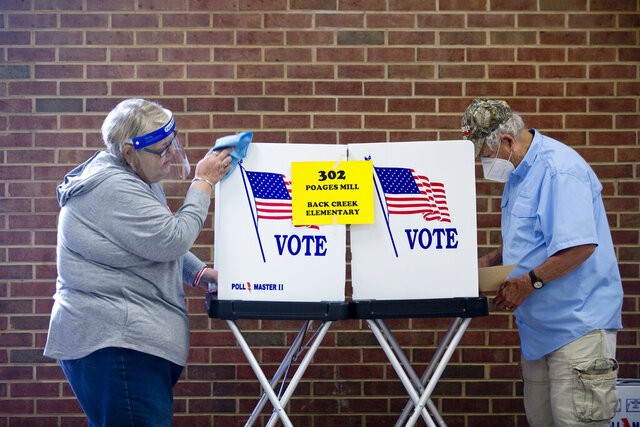 Glenda Patsel, left, wipes down a voting booth  as Bobby J. Lambert fills out his ballot for the senate Republican candidates primary election, Tuesday, June 23, 2020, at Hidden Valley Middle School in Roanoke, Va. (Stephanie Klein-Davis/The Roanoke Times via AP)