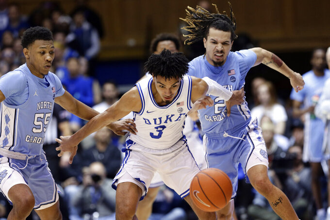 Duke guard Tre Jones (3) chases the ball with North Carolina guard Christian Keeling (55) and guard Cole Anthony (2) during the first half of an NCAA college basketball game in Durham, N.C., Saturday, March 7, 2020. (AP Photo/Gerry Broome)