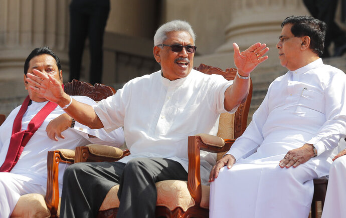 Sri Lankan president Gotabaya Rajapaksa, center, speaks with his cabinet colleagues in Colombo, Sri Lanka, Friday, Nov. 22, 2019. Rajapaksa, who was elected last week, said he would call a parliamentary election as early as allowed. The parliamentary term ends next August, and the constitution allows the president to dissolve Parliament in March and go for an election. (AP Photo/Eranga Jayawardena)