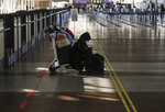 A lone passenger sits near the empty check-in area for Latam airplanes at the Arturo Merino Benitez airport in Santiago, Chile, Tuesday, May 26, 2020. South America's biggest carrier is seeking U.S. bankruptcy protection as it grapples with a sharp downturn in air travel sparked by the coronavirus pandemic. (AP Photo/Esteban Felix)