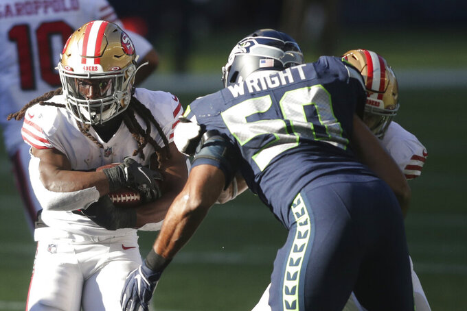 San Francisco 49ers running back JaMycal Hasty, left, tries to get past Seattle Seahawks outside linebacker K.J. Wright (50) during the first half of an NFL football game, Sunday, Nov. 1, 2020, in Seattle. (AP Photo/Scott Eklund)