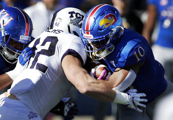 Kansas running back Khalil Herbert (10) is tackled by TCU linebacker Ty Summers (42) during the first half of an NCAA college football game in Lawrence, Kan., Saturday, Oct. 27, 2018. (AP Photo/Orlin Wagner)