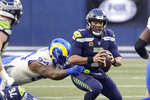 Seattle Seahawks quarterback Russell Wilson, right, eyes a receiver as Los Angeles Rams defensive tackle A'Shawn Robinson grabs him during the second half of an NFL wild-card playoff football game, Saturday, Jan. 9, 2021, in Seattle. (AP Photo/Ted S. Warren)