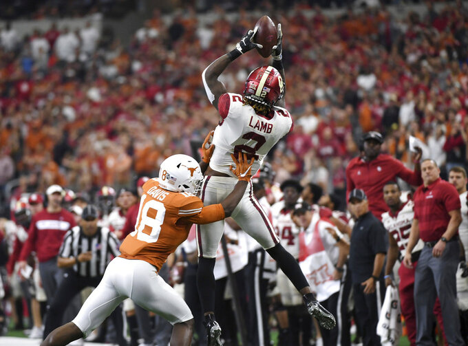 Oklahoma wide receiver CeeDee Lamb (2) makes a key reception over Texas defensive back Davante Davis (18) during the first half of the Big 12 Conference championship NCAA college football game on Saturday, Dec. 1, 2018, in Arlington, Texas. (AP Photo/Jeffrey McWhorter)