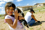 FILE - In this Tuesday, April 17, 2007 file photo, Cheyenne Yazzi hugs her puppy while her mother, Selina, pulls weeds in their backyard in Churchrock, N.M. Activists are using virtual reality technology to focus on areas of the Navajo Nation, like Churchrock, affected by uranium contamination. (Brian Leddy/Gallup Independent via AP, File)