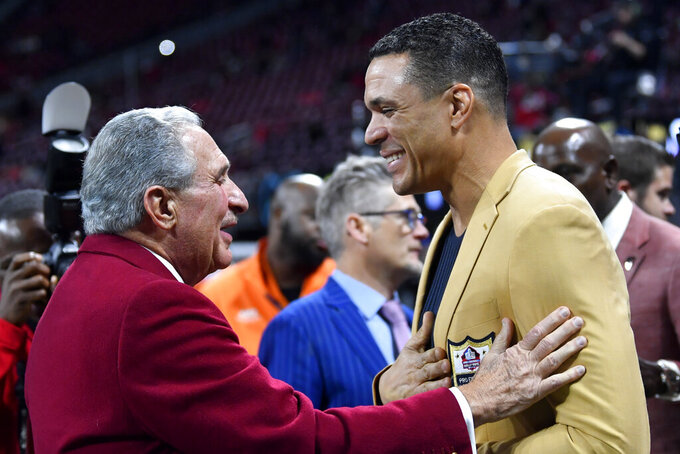 Atlanta Falcons owner Arthur Blank, left, speaks with former NFL player and Football Hall of Fame player Tony Gonzalez before the first half of an NFL football game between the Atlanta Falcons and the New Orleans Saints, Thursday, Nov. 28, 2019, in Atlanta. (AP Photo/John Amis)