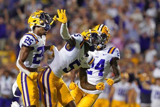 LSU safety Jay Ward (5) celebrates with cornerback Cordale Flott (25) and cornerback Darren Evans (24) after breaking up a pass in the first half of an NCAA college football game against Auburn in Baton Rouge, La., Saturday, Oct. 2, 2021. (AP Photo/Gerald Herbert)