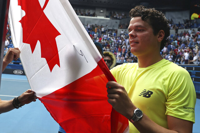 Canada's Milos Raonic signs his autograph onto a Canadian flag after defeating Croatia's Marin Cilic in their fourth round singles match at the Australian Open tennis championship in Melbourne, Australia, Sunday, Jan. 26, 2020. (AP Photo/Dita Alangkara)