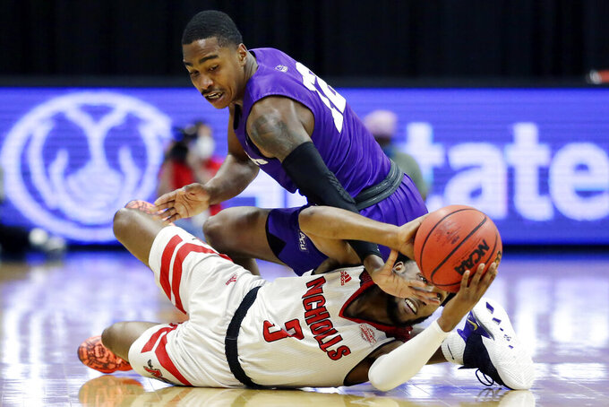 Abilene Christian guard Mahki Morris, top, reaches for the ball as Nicholls State guard Kevin Johnson (3) gathers it up during the first half of an NCAA college basketball game for the Southland Conference men's tournament championship Saturday, March 13, 2021, in Katy, Texas. (AP Photo/Michael Wyke)