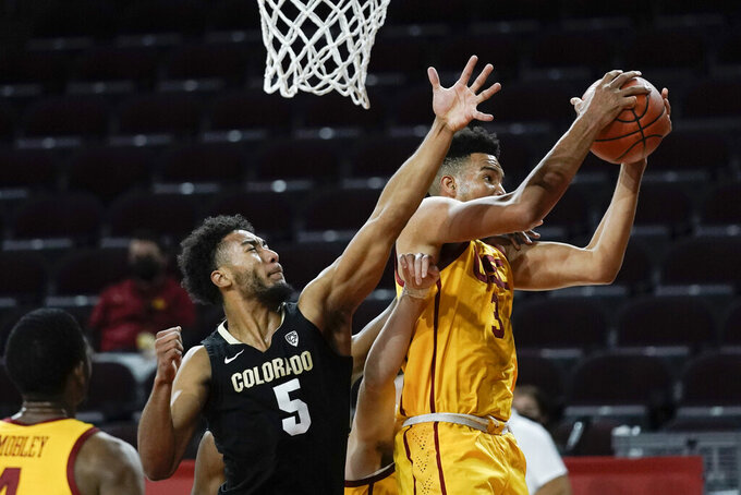 Southern California's Isaiah Mobley, right, gets a rebound next to Colorado's D'Shawn Schwartz during the first half of an NCAA college basketball game Thursday, Dec. 31, 2020, in Los Angeles. (AP Photo/Jae C. Hong)