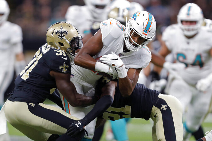 Miami Dolphins wide receiver Brice Butler (17) carries as New Orleans Saints defensive back Chris Banjo (31) and defensive back Patrick Robinson (21) tackle in the first half of an NFL preseason football game in New Orleans, Thursday, Aug. 29, 2019. (AP Photo/Gerald Herbert)