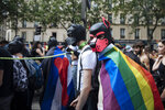Participants wear dog masks during the annual Gay Pride march in Paris, Saturday, June 26, 2021. This year's march in Paris comes amid widespread fury and concern in Europe about legislation in EU-member nation Hungary that will ban showing content about LGBT issues to children. (AP Photo/Lewis Joly)