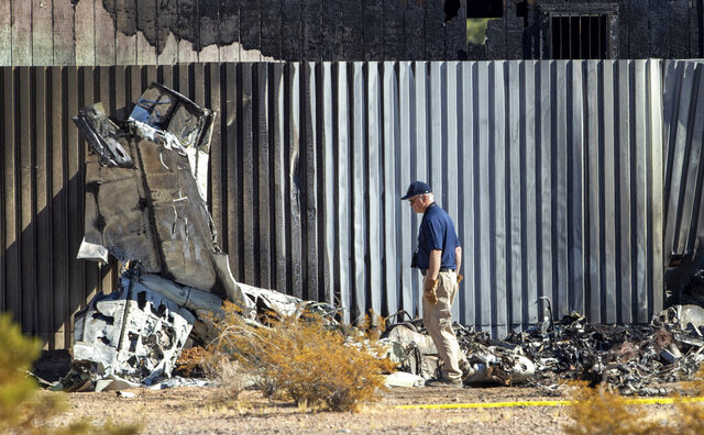 An investigator looks at the site of a deadly plane crash Thursday, Oct. 29, 2020, in Las Vegas. A twin-engine aircraft crashed shortly after takeoff Thursday, killing two people and igniting a fire that damaged a construction trailer from which a man escaped while choking on fuel fumes. (Steve Marcus/Las Vegas Sun via AP)