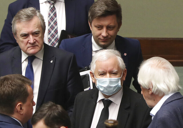 Poland's ruling party leader Jaroslaw Kaczynski, center, wearing an anti-coronavirus mask and members of the government following a vote in parliament that approved legislation for all-postal voting after Sunday presidential election was postponed due to organizational problems, in Warsaw, Poland, Thursday, May 7, 2020. The ruling party says that July 12 is the possible new date for the election that will be all-postal.(AP Photo/Czarek Sokolowski)