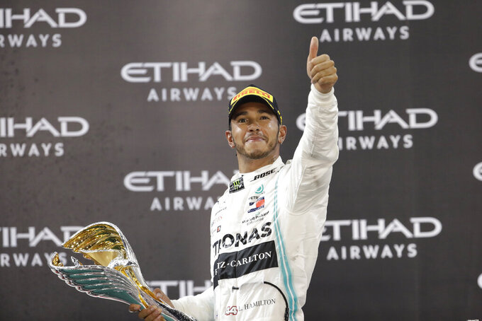 Mercedes driver Lewis Hamilton of Britain celebrates on the podium after wining the Emirates Formula One Grand Prix, at the Yas Marina racetrack in Abu Dhabi, United Arab Emirates, Sunday, Dec.1, 2019. (AP Photo/Luca Bruno)