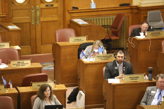 In this photo provided by Patrick Callahan, several House lawmakers sit at their desks on the House floor while they debated and voted through a teleconference system Monday March 30, 2020, in Pierre, S.D.. Rep. Julie Frye-Mueller, a Rapid City Republican, wore a mask and gloves due to the coronavirus pandemic. They were considering emergency bills pushed by Gov. Kristi Noem. (Patrick Callahan/South Dakota Broadcasters Association via AP)