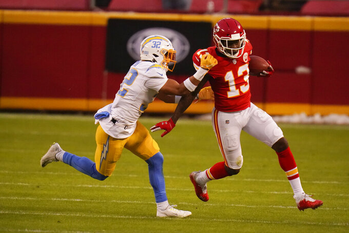 Kansas City Chiefs wide receiver Byron Pringle, right, runs from Los Angeles Chargers safety Alohi Gilman after catching a pass during the first half of an NFL football game, Sunday, Jan. 3, 2021, in Kansas City. (AP Photo/Jeff Roberson)