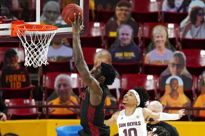 San Diego State forward Nathan Mensah, left, goes in for a dunk as he gets past Arizona State guard Jaelen House (10) during the first half of an NCAA college basketball game Thursday, Dec. 10, 2020, in Tempe, Ariz. (AP Photo/Ross D. Franklin)